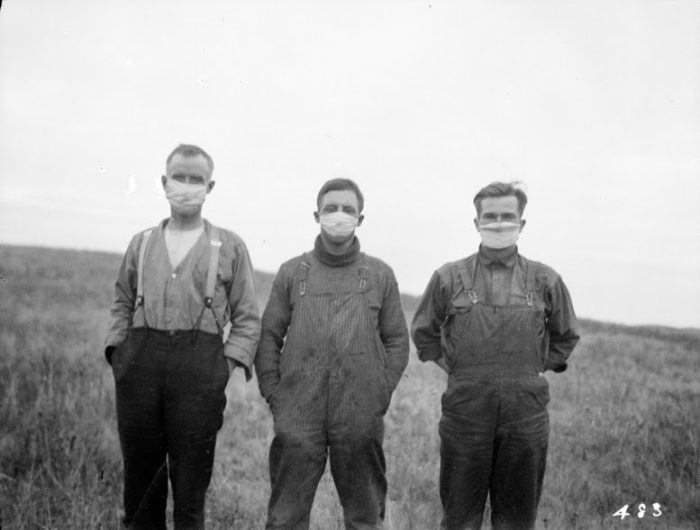 black and white photo of three men wearing masks on an Alberta farm during the 1918 pandemic