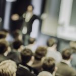 Defocused shot of crowd in the lecture hall. Purposely blurred with a lens.