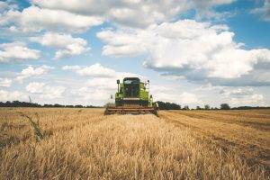 Caption reads: A scenario in which a tractor guidance device could be used. Picture shows green tractor grazing over land in perfectly parallel lines with clouds in the sky above.